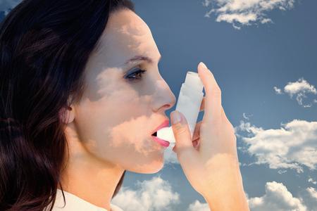 inhaler: Asthmatic brunette using her inhaler  against blue sky