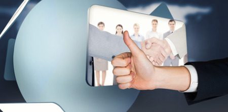 inter: Hand showing thumbs up against screen displaying handshake and business people in digital inter