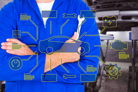 Male mechanic holding spanner on white background against auto repair shop Stock Photo