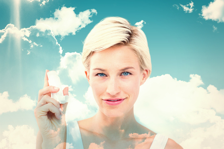 affliction: Pretty woman holding inhaler smiling at camera  against blue sky