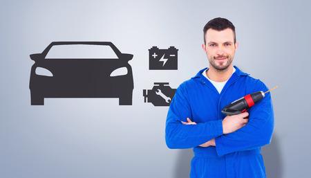power drill: Confident handyman holding power drill against grey vignette