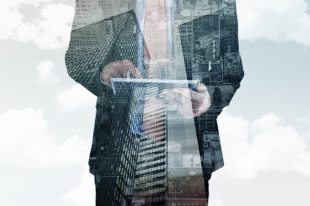 scrolling: Businessman scrolling on his digital tablet against low angle view of skyscrapers Stock Photo