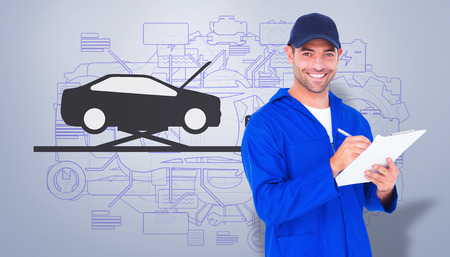 car mechanic: Portrait of happy male mechanic writing on clipboard against grey vignette Stock Photo