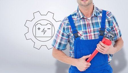 plumber: Cropped image of plumber holding monkey wrench against grey vignette