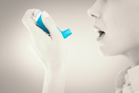 asthma: Close up of a woman using an asthma inhaler against grey vignette