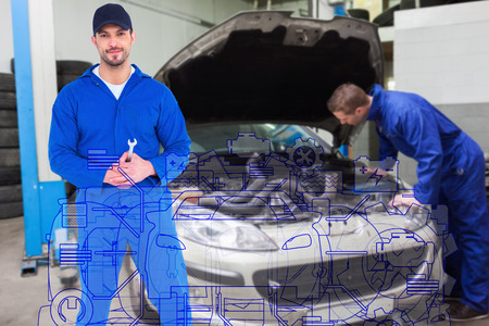 Smiling male mechanic holding spanner against mechanic examining car engine Stock Photo