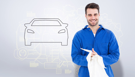 wiping: Male mechanic wiping hands with cloth against grey vignette Stock Photo