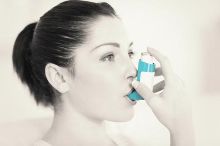 asma: Mujer que tiene asma usando el inhalador para el asma por ser saludable