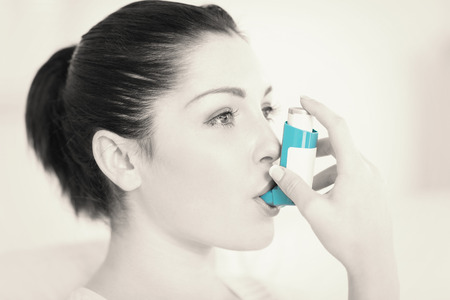 asthma: Woman having asthma using the asthma inhaler for being healthy Stock Photo