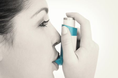 Woman with an asthma inhaler against white background