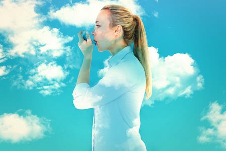 inhaler: Beautiful blonde using an asthma inhaler against blue sky
