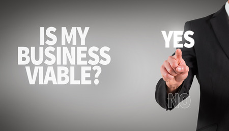 viable: Businessman standing and pointing against grey vignette Stock Photo