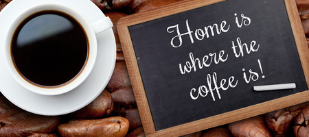 where to eat: White cup of coffee against chalkboard with piece of chalk
