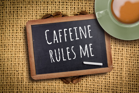 drink me: Green cup of coffee against chalkboard with piece of chalk