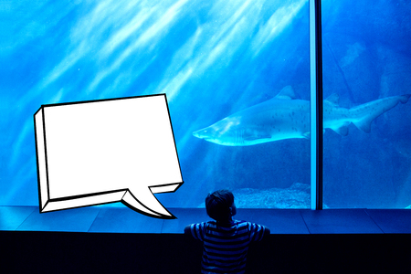 Speech bubble against young man looking at a shark in a tank
