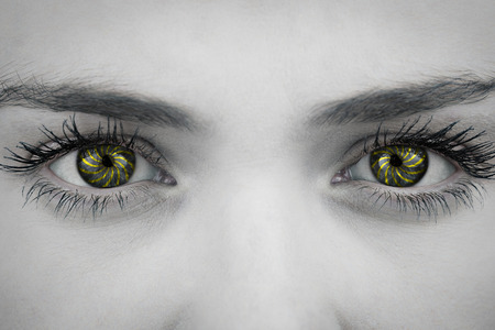 close up eyes: Close up of female blue eyes against spiral Stock Photo