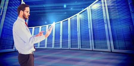 scrolling: Businessman scrolling on his digital tablet against composite image of server towers Stock Photo
