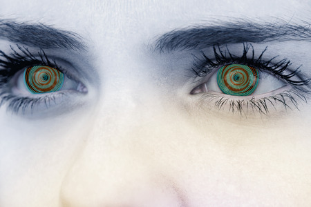 hypnotize: Close up of female blue eyes against spiral Stock Photo