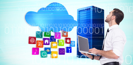 sophisticated: Sophisticated businessman standing using a laptop  against composite image of cloud with apps