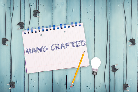 hand crafted: The word hand crafted against notepad and plug on wooden background