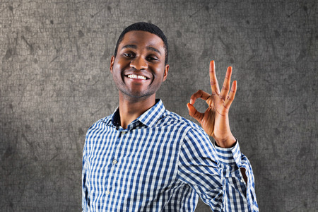 alright: Happy businessman making ok sign against grey background Stock Photo