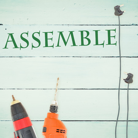 assemble: The word assemble against tools on wooden background