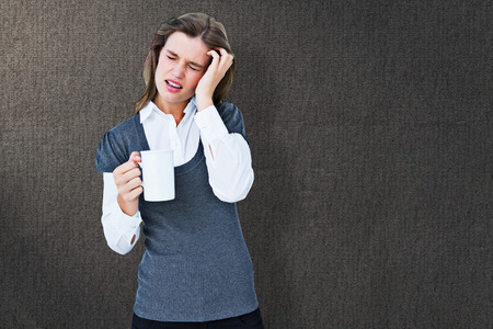 wincing: Woman with headache holding mug  against grey background Stock Photo