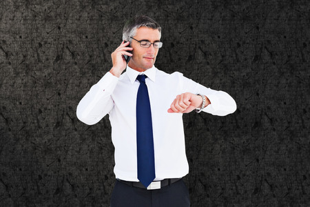 wrist watch: Businessman on the phone looking at his wrist watch against grey background