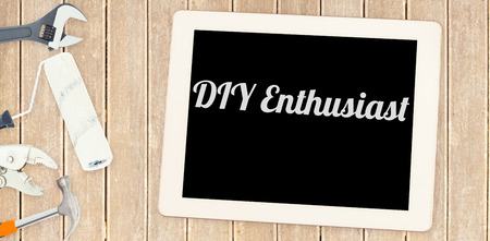 enthusiast: The word diy enthusiast against tools and tablet on wooden background