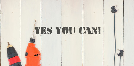 aspirational: The word yes you can! against diy tools on wooden background