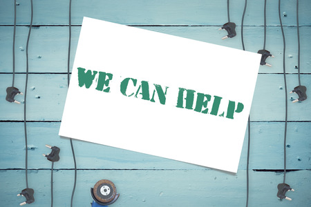 can we help: The word we can help and white card against plugs on wooden background