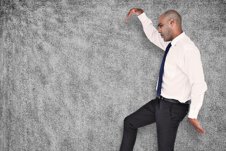 stepping: Businessman stepping against grey background