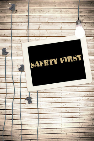safety first: The word safety first against tablet and plugs on wooden background