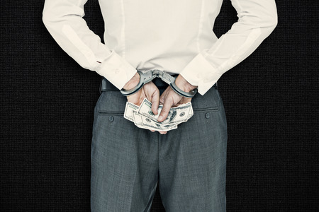 restraining device: Businessman in handcuffs holding bribe against black background