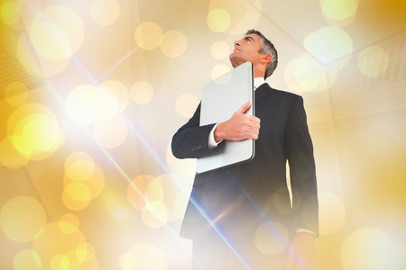light spot: Businessman in suit holding his laptop proudly against yellow abstract light spot design Stock Photo