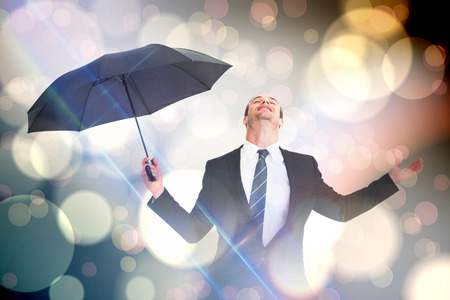 sheltering: Businessman sheltering under black umbrella testing against light glowing dots design pattern