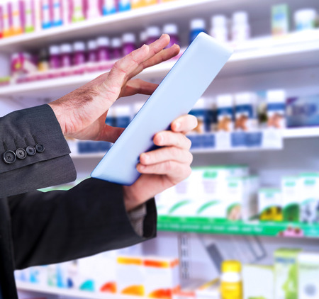 scrolling: Businessman scrolling on his digital tablet against close up of shelves of drugs