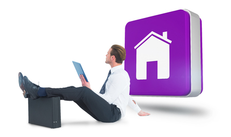 feet up: Businessman using tablet with feet up on briefcase against app tile Stock Photo