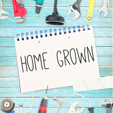 grown: The word home grown against tools and notepad on wooden background