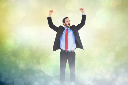 Happy cheering businessman raising his arms against green abstract light spot design Stock Photo