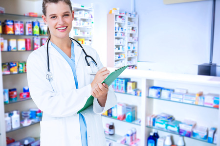grey hair: Happy doctor writing on clipboard against pharmacist with grey hair standing behind shelves of drugs