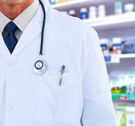 bata de laboratorio: Médico con bata de laboratorio en contra de cerca de los estantes de las drogas