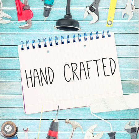 hand crafted: The word hand crafted against tools and notepad on wooden background