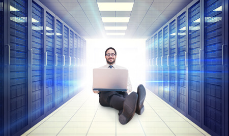 database server: Businessman using laptop against digitally generated server room with towers