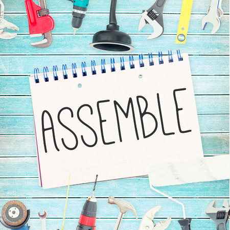 assemble: The word assemble against tools and notepad on wooden background
