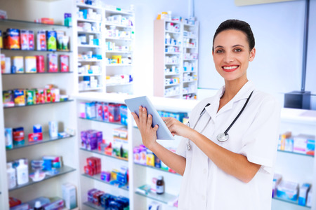 pharmacist: Pretty nurse using tablet pc against pharmacist with grey hair standing behind shelves of drugs Stock Photo
