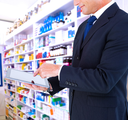 arms out: Mid section of a businessman with arms out against close up of shelves of drugs