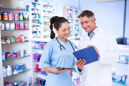grey hair: Doctor and nurse looking at clipboard against pharmacist with grey hair standing behind shelves of drugs