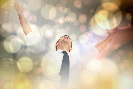 Handsome businessman cheering with arms up against light glowing dots design pattern Stock Photo