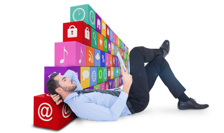 using tablet: Businessman lying on floor using tablet  against app wall